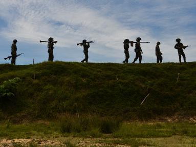 Sejumlah prajurit TNI dari batalyon infantri Raider 112 berjalan membawa berbagai senjata selama latihan menembak di Mata Ie, Aceh Besar, Aceh, Selasa (11/6/2019). Latihan menembak ini untuk memelihara dan meningkatkan kemampuan prajurit Raider.  (AFP Photo/Chaideer Mahyuddin)