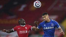 Striker Liverpool, Sadio Mane, duel udara dengan pemain Everton, Mason Holgate, pada laga Liga Inggris di Stadion Anfield, Minggu (21/2/2021). Everton menang 2-0 atas Liverpool. (Lawrence Griffiths/ Pool via AP)