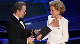 Gary Oldman saat menerima penghargaan dalam Oscar 2018 di Dolby Theater, Los Angeles, Amerika Serikat, Minggu (4/3). Perannya sebagai Winston Churchill di Darkest Hour berhasil membawa pulang Oscar. (Chris Pizzello/Invision/AP)