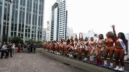 Juru foto mengambil gambar dari belasan wanita seksi yang berpose di Paulista Avenue, Sao Paulo, Senin (8/8). Mengenakan bikini, para wanita tersebut mempromosikan kontes Miss BumBum 2016. (Miguel SCHINCARIOL/AFP)