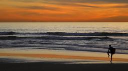 Pemain surfing saat menikmat matahari terbenam di Cardiff, California (27/1/2016). Wilayah Selatan California ini usai di landa Badai El Nino. (REUTERS/Mike Blake)