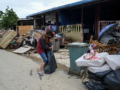 Seorang wanita memeluk anak di dekat puing-puing dan barang-barang di luar rumah mereka, setelah banjir surut di Mentakab, negara bagian Pahang Malaysia (11/1/2021). Banjir yang melanda daerah tersebut, membuat  Puluhan ribu warga dievakuasi. (AFP/Mohd Rasfan)