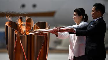 Atlet peraih tiga kali medali emas olimpiade, Tadahiro Nomura dan Saori Yoshida, menyalakan obor Olimpiade saat tiba dari Yunani di Pangkalan Udara Matsushima, Jepang, Jumat (20/3). Prosesi menuju Olimpiade Tokyo 2020 masih terus berjalan.(AFP/Philip Fong)
