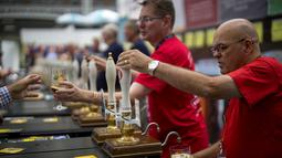 Staf bar melayani penggemar bir selama The Great British Beer Festival di Kensington Olympia di London barat (6/8/2019). Great British Beer Festival tahunan ini diadakan 6-10 Agustus 2019. (AFP Photo/Tolga Akmen)