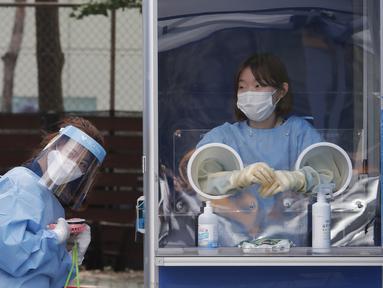 Seorang pekerja medis memegang kipas angin portabel selama panas terik sementara petugas polisi menjalani tes COVID-19 di klinik darurat di Badan Kepolisian Metropolitan Seoul di Seoul, Korea Selatan, Rabu, (19/8/2020). (AP Photo / Ahn Young -joon)