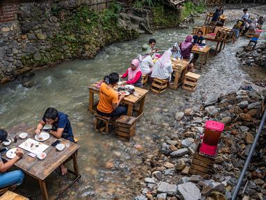 Pelanggan menikmati makan siang di sebuah restoran dengan meja yang berada di tengah aliran sungai di Kampung Kemensah di pinggiran Kuala Lumpur, Malaysia, Selasa (14/7/2020). Tak perlu khawatir, air sungai yang datang dari bukit ini masih bersih dan menyegarkan. (Photo by Mohd RASFAN / AFP)
