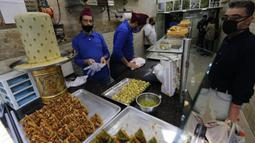 Seorang pria membeli penganan manis saat Ramadan di tengah pandemi COVID-19 di Beirut, Lebanon pada Minggu (26/4/2020). Makanan manis dan minuman segar biasanya yang jadi buruan utama untuk berbuka puasa saat bulan suci Ramadan. (Xinhua/Bilal Jawich)