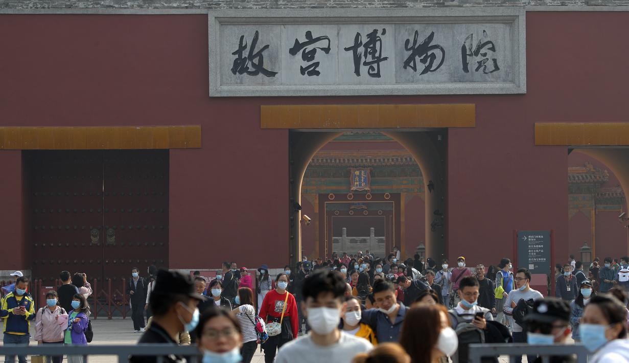 Pengunjung yang mengenakan masker untuk membantu mencegah penyebaran virus corona keluar dari Kota Terlarang selama liburan selama seminggu untuk Hari Nasional 1 Oktober, di Beijing, Rabu, (7/10/2020). (AP Photo/Andy Wong)