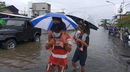 Warga menerobos banjir yang menggenangi daerah Kaligawe, Kota Semarang, Selasa (9/2/2021). Banjir yang menggenangi daerah Kaligawe sejak beberapa hari lalu hingga Selasa (9/2) pagi masih belum surut dan mengakibatkan mobilitas warga menjadi terhambat. (Liputan6.com/Gholib)
