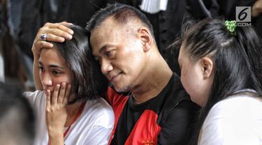 Aktor Tio Pakusadewo merangkul sang anak, Risa (kiri) dan keponakannya, Namira saat menunggu sidang  kasus penyalahgunaan narkoba di Pengadilan Negeri Jakarta Selatan, Kamis (28/6). Sidang beragenda pembacaan pledoi oleh Tio. (Liputan6.com/Faizal Fanani)