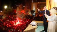 Presiden Turki Recep Tayyip Erdogan dan istri, Emine menyapa pendukung Partai Keadilan dan Pembangunan (AKP) di Ankara, Turki, Senin (25/6). Erdogan kembali memenangkan pemilu presiden di Turki. (Presidency Press Service via AP, Pool)