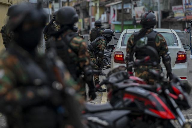 Personel keamanan memeriksa kendaraan di pos pemeriksaan saat negara itu bersiap untuk lockdown di Kolombo, Selasa (25/5/2021). Sri Lanka bersiap menerapkan lockdown ketat selama dua minggu untuk menekan penyebaran corona Covid-19. (ISHARA S. KODIKARA / AFP)