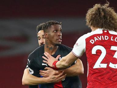 Striker Crystal Palace, Wilfried Zaha (kiri) dan bek Arsenal, David Luiz terlibat pertikaian dalam laga lanjutan Liga Inggris 2020/21 di Emirates Stadium, Kamis (14/1/2021). Crystal Palace bermain imbang 0-0 dengan Arsenal. (AFP/Julian Finney/Pool)