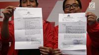 Sekjen PSI, Raja Juli Antoni (kiri) menunjukkan Surat Perintah Penghentian Penyidikan (SP3) usai menggelar konferensi pers di kantor DPP PSI, Jakarta, Jumat (1/6). (Liputan6.com/Herman Zakharia)