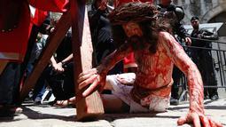 Seorang aktor berpakaian seperti Yesus Kristus terjatuh saat melakukan prosesi Jalan Salib menyusuri Via Dolorosa menuju Gereja Makam Suci di Kota Tua Yerusalem, Jumat (19/4). Prosesi Jalan Salib melewati jalan-jalan kecil di Kota Tua Yerusalem. (AP Photo/Ariel Schalit)
