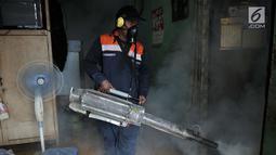 Petugas melakukan penyemprotan asap (fogging) nyamuk demam berdarah dengue (DBD) di salah satu rumah warga RW 01, Kelurahan Cipinang, Jakarta, Minggu (10/3). Fogging ini juga untuk membasmi perkembangbiakan jentik nyamuk. (merdeka.com/Iqbal Nugroho)