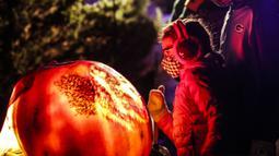 Pengunjung mengamati ukiran labu dalam acara Malam 1.000 Jack-O'-Lantern di Chicago Botanic Garden, Glencoe, Illinois, Amerika Serikat, 24 Oktober 2020. Lebih dari 1.000 labu ukiran tangan dipamerkan di acara tersebut menjelang perayaan Halloween. (Xinhua/Joel Lerner)