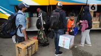 Pemudik memasukkan bawaan ke dalam bagasi bus di terminal bayangan di Pasar Jumat, Jakarta, Rabu (5/5/2021). Jelang pemberlakuan larangan mudik 2021 pada esok hari, sejumlah terminal bayangan di wilayah Jabodetabek dipadati para pemudik tujuan Pulau Jawa dan Sumatera. (merdeka.com/Arie Basuki)