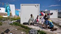 Sejumlah anak pengungsi bermain di depan Kamp Oinofyta, Athena, Yunani (13/3). Kamp Oinofyta yang merupakan gedung bekas pabrik. (AFP Photo / Louisa Gouliamaki)