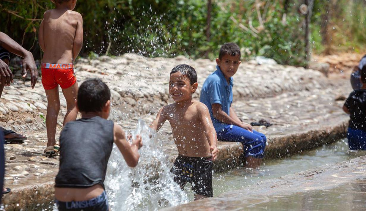 Anak-anak Palestina menikmati waktu bermain di sebuah mata air alami di tengah gelombang panas di Kota Jericho, Tepi Barat, (18/5/2020). (Xinhua/Luay Sababa)