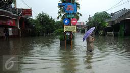 Warga melintasi banjir di perumahan Pondok Hijau Permai, Bekasi, Senin (20/2). Ketinggian air yang merendam perumahan Pondok Hijau Permai mencapai 30-70 cm. (Liputan6.com/Gempur M. Surya)