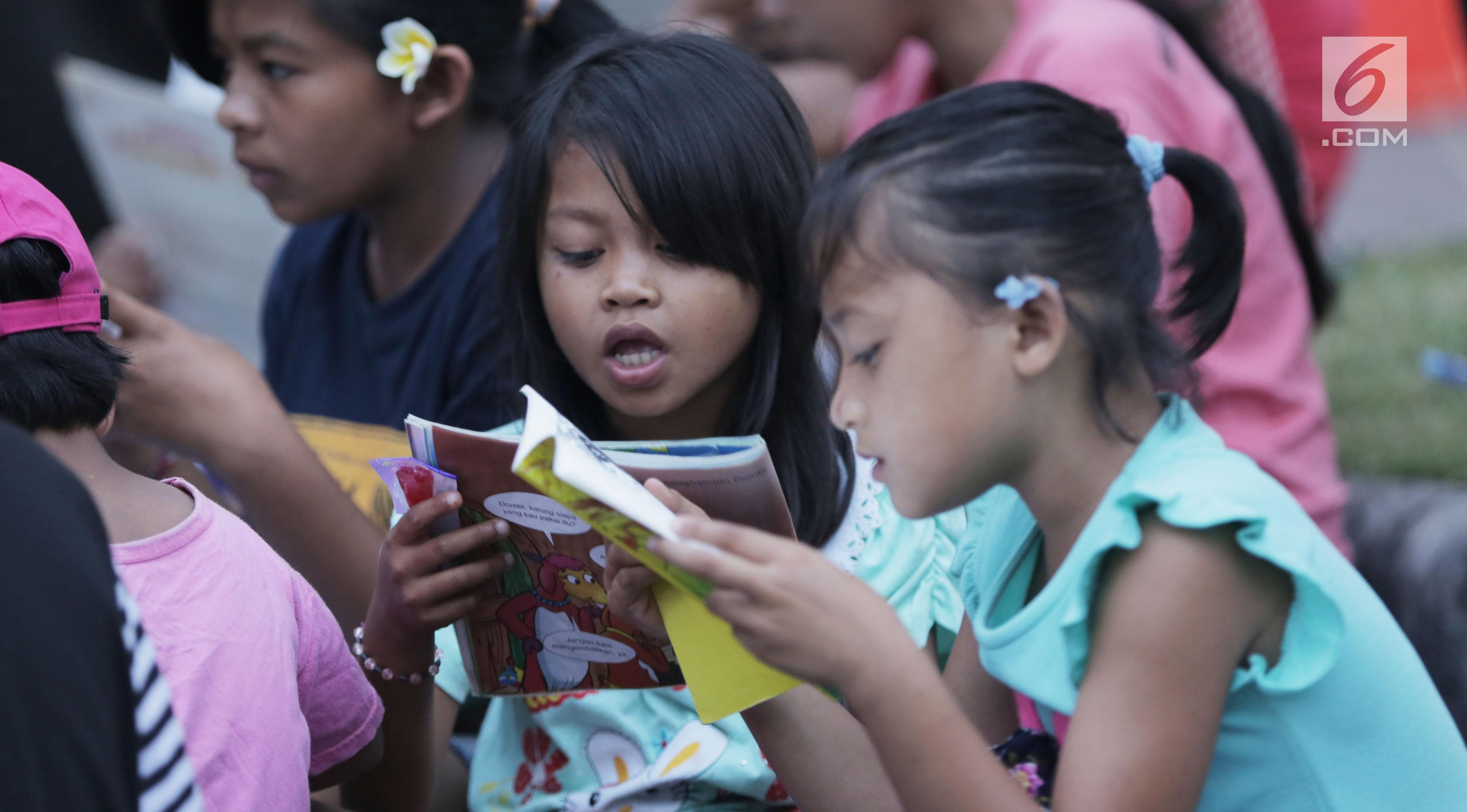 Sejumlah anak membaca buku di mobil Perpustakaan Keliling Dinas Perpustakaan dan Arsip Daerah Kabupaten Klungkung di lokasi pengungsian korban evakuasi Gunung Agung, Klungkung, Bali, Sabtu (30/09). (Liputan6.com/Gempur M Surya)