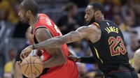 LeBron James (kanan) mencuri bola dari pemain Raptors, Serge Ibaka (AP Photo/Tony Dejak)