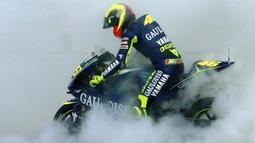 Valentino Rossi melakukan burnout ketika merayakan kemenangan dalam balapan MotoGP di sirkuit Ricardo Tormo, Spanyol pada 31 Oktober 2004. (AFP/Jose Jordan)