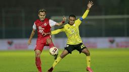 Bek Persija Jakarta, Rezaldi Hehanusa (kiri), berebut bola dengan penyerang Barito Putera, Rizky Pora, pada laga perempat final Piala Menpora 2021 di Stadion Kanjuruhan, Malang, Sabtu (10/4/2021). Persija Jakarta menang dengan skor 1-0. (Bola.com/Arief Ba