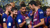 Pemain Barcelona melihat Piala Super Spanyol usai pertandingan melawan Sevilla di Tangier, Maroko, (13/8). Barcelona meraih gelar ke-13 di Piala Super Spanyol terbanyak ketimbang tim lain. (AP Photo/Mosa'ab Elshamy)