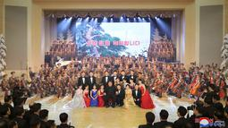 Pemimpin Korea Utara Kim Jong-un berpose dengan pengisi acara pertunjukan Tahun Baru Imlek di Pyongyang, dalam foto tak bertanggal yang dirilis oleh KCNA pada Jumat (12/2/2021). Tepat 12 Februari tahun ini, etnis Tionghoa di seluruh dunia kembali merayakan momen Imlek. (KCNA VIA KNS/AFP)