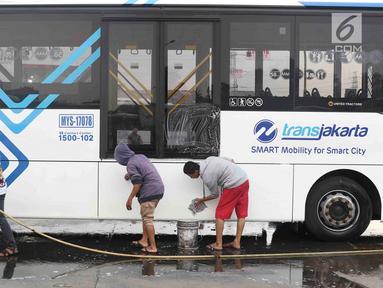 Suporter Persija Jakarta mencuci bus transjakarta di kantor PT Transjakarta, Jakarta, Kamis (13/12). Hal tersebut dilakukan bentuk tanggung jawab atas aksi vandalisme oknum suporter saat Persija meraih Juara Liga 1 2018. (Liputan6.com/Immanuel Antonius)