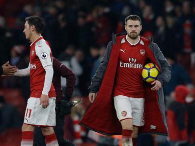 Pemain Arsenal Aaron Ramsey (kanan) membawa bola usai pertandingan melawan Everton dalam Liga Inggris di Stadion Emirates, London (3/2). Dalam pertandingan ini Aaron Ramsey berhasil menyumbang tiga gol untuk Arsenal. (AP Photo / Alastair Grant)