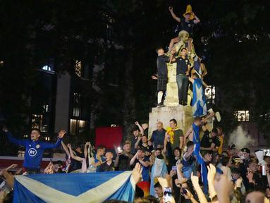 Suporter Skotlandia berkumpul dan merayakan keberhasilan negaranya menahan imbang Inggris pada laga Euro 2020 di patung William Shakespeare di Leicester Square, London, Jumat (18/6/2021). (AP/Kirsty Wigglesworth)