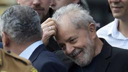Mantan Presiden Brasil Luiz Inacio Lula da Silva tersenyum sambil mengaruk kepalanya setelah dibebaskan di Curitiba, Brasil, (8/11/2019). Mantan presiden yang kini berusia 74 tahun itu, pemimpin Brasil selama 2003 hingga 2010, dipandang sebagai ikon kiri di negara itu. (AFP Photo/Carl De Souza)