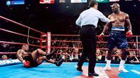 Evander Holyfield berhasil memukul jatuh Mike Tyson pada ronde keenam dalam duel perebutan sabuk juara dunia kelas berat versi WBA di MGM Grand Garden Arena, Las Vegas, 9 November 1996. Holyfield akhirnya menang TKO atas Tyson. (AFP/JEFF HAYNES)