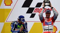 Valentino Rossi (kiri) bersama juara MotoGP Malaysia 2016 Andrea Dovizioso (kanan). (MANAN VATSYAYANA / AFP)