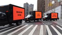 Tiga mobil box yang membawa billboard yang bertema kepedulian untuk Suriah turun ke jalan mengelilingi gedung Perserikatan Bangsa-Bangsa (PBB) di New York (22/2). (AFP Photo/Timothy A. Clary)