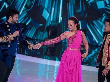 Pedangdut Fildan (kanan) melihat Ridho Rhoma (kiri) menggenggam tangan Zaskia Gotik (tengah) saat tampil dalam Indonesian Dangdut Awards 2018 di Jakarta, Jumat (12/10). Mereka membawakan lagu Koi Mil Gaya dan Tum Hi Ho. (Liputan6.com/Faizal Fanani)