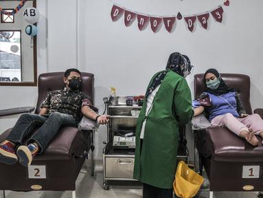 Warga melakukan donor darah di Kantor PMI Jakarta Timur, Rabu (28/7/2021). Tiap harinya, PMI Jakarta Timur melayani 20-30 pendonor darah meski jumlah menurun akibat pandemi COVID-19 ditambah keterbatasan akses warga saat PPKM. (merdeka.com/Iqbal S. Nugroho)