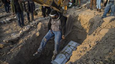 Seorang pria naik backhoe usai membantu memasukkan peti mati berisi jenazah Vicenta Panduro Panduro (87) yang meninggal karena komplikasi COVID-19 saat pemakaman di Carabayllo, Lima, Peru, Selasa (25/8/2020). Total kasus COVID-19 di Peru mencapai 600 ribu. (AP Photo/Rodrigo Abd)