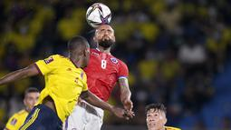 Gelandang Chile Arturo Vidal menyundul bola di bawah pengawasan gelandang Kolombia Matheus Uribe pada lanjutan Kualifikasi Piala Dunia 2022 zona Amerika Selatan di Estadio Metropolitano Roberto Meléndez, Jumat (10/9/2021). Dua gol Miguel Borja memastikan Kolombia menang 3-1.  (AP/Fernando Vergara)