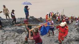 Para penyelamat mengangkut jasad seorang korban usai terjadinya insiden tanah longsor di lokasi penambangan batu giok di Hpakant, Negara Bagian Kachin, Myanmar (2/7/2020). Jumlah korban jiwa dalam bencana tanah longsor tersebut bertambah menjadi 113 orang. (Xinhua/Departemen Pemadam Kebakaran Myanma