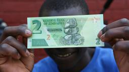 Seorang warga memegang salah satu uang kertas baru yang dikeluarkan Reserve Bank of Zimbabwe di Harare, 12 November 2019. Pemerintah Zimbabwe memperkenalkan kembali mata uang negaranya setelah hampir satu dekade terakhir menggunakan mata uang negara lain untuk bertransaksi. (AP/Tsvangirayi Mukwazhi)