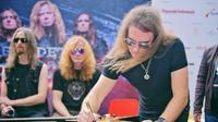 Para personel Megadeth yang menandatangani gitar untuk donasi korban gempa
