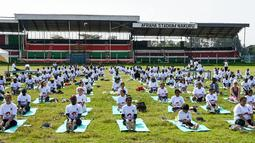 Ratusan warga melakukan gerakan yoga saat mengikuti yoga massal di Stadion Afraha, Nakuru, Kenya (15/6/2019). Hari Yoga Internasional, yang setiap tahun dirayakan pada 21 Juni, pertama kali diusulkan Perdana Menteri India Narendra Modi pada 2014 ke Majelis Umum PBB. (AFP Photo/Suleiman Mbatiah)