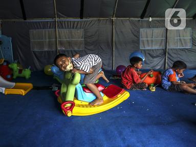 Anak-anak pengungsi Gunung Merapi bermain kuda-kudaan di Barak Pengungsian Glagaharjo, Cangkringan, Sleman, Yogyakarta, Jumat (20/11/2020). Para relawan menyediakan berbagaai fasilitas bermain seperti puzle, kuda-kudaan, ayunan hingga prosotan. (Liputan6.com/Johan Tallo)