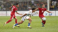 Pemain Timnas U-22,  M Rezaldi Hehanusa dan Evan Dimas berusaha merebut bola pada pêrtandíngan Sepak Bola Indonesia melawan Malaysia di Stadion Shah Alam, Selangor, Sabtu (26/08). Indonesia kalah 0-1 dari tuan rumah Malaysia. (Liputan6.com/Faizal Fanani)