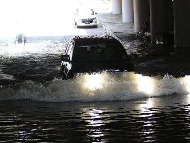 Kendaraan melintasi terowongan Apron Kemayoran yang tergenang air, Jakarta, Selasa (11/9). Terowongan Apron, Jalan HBR Motik, Kemayoran, Jakarta Pusat, tergenang air karena ada sumbatan di saluran air dari 2 minggu lalu. (Liputan6.com/Herman Zakharia)