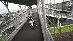Pengendara sepeda motor melewati Jembatan Penyeberangan Orang (JPO) di kawasan Pasar Minggu, Jakarta, Selasa (17/10). JPO yang merupakan hak para pejalan kaki justru digunakan pemotor untuk menyeberang. (Liputan6.com/Immanuel Antonius)